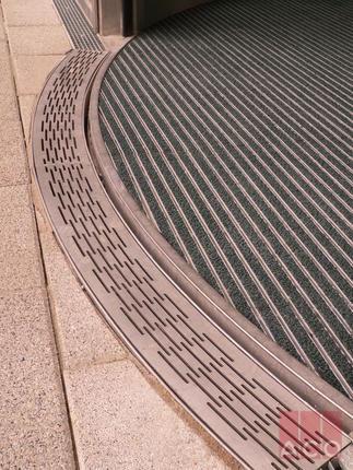 Körforgós portálajtó vízelvezetését egyedi íves kialakítású rozsdamentes acélból készült ACO folyókával oldották meg.