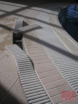 Medencetér csurgalékvizét ACO Modular típusú rozsdamentes rácsos folyókával oldották meg, műanyag ráccsal.